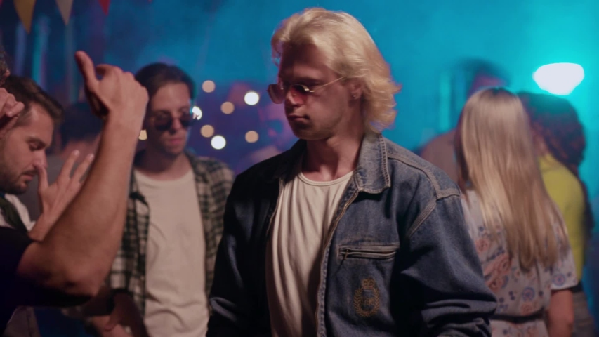 Cheerful handsome urban youth dancing on cool night party. In focus appealing blonde guy doing modern moves into music with his friends. | Shutterstock HD Video #1036040861