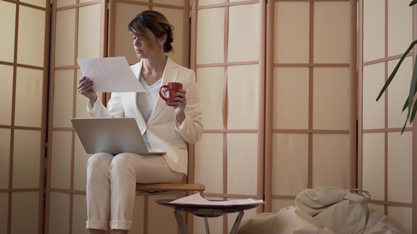 Mature caucasian business woman in a white formal suit drinking coffee and looking at a laptop screen and paper sitting at home. Woman kneads stiff neck. Slow motion.   Shutterstock HD Video #1036096661