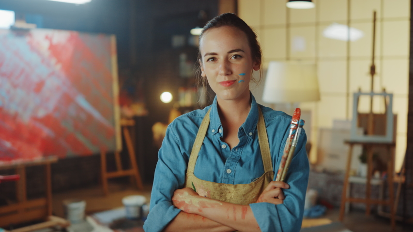 Talented Young Female Artist Dirty with Paint, Wearing Apron, Crosses Arms while Holding Brushes, Looks at the Camera with a Smile. Authentic Creative Studio with Large Canvas. Zoom in Portrait | Shutterstock HD Video #1036107671