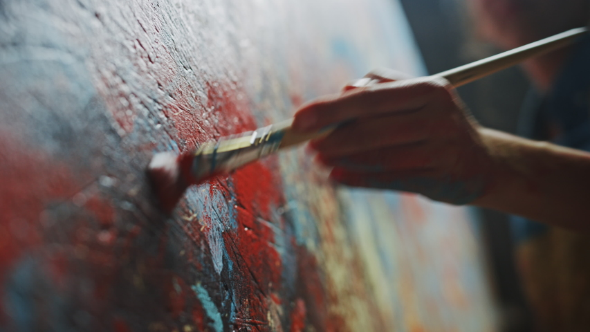 Close-up Shot of Artist Hand, Holding Paint Brush and Drawing Painting with Red Paint. Colorful, Emotional Oil Painting. Contemporary Painter Creating Modern Abstract Piece of Art | Shutterstock HD Video #1036107761