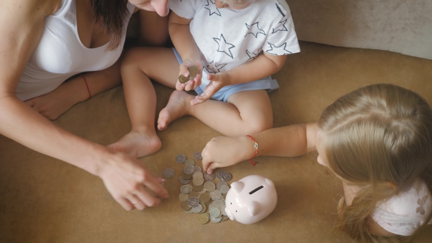 Mother and two children saving money to piggy bank. Family earning money for future. Investment concept. | Shutterstock HD Video #1036162091
