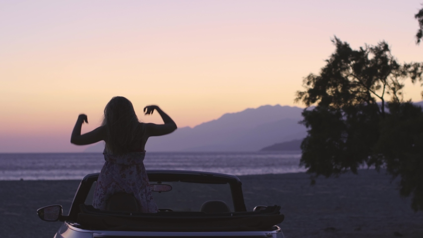 Young pretty womanenjoy white convertible vintage car on exotic island by seaside at sunset. Beautiful girl have fun in cabriolet.Dream,adventure,recreation, vacation, road trip and freedom concept. | Shutterstock HD Video #1036209851