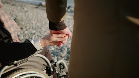 Sincere love and devotion. Man holding hand of his beloved disabled woman in wheelchair. They enjoying sea view together