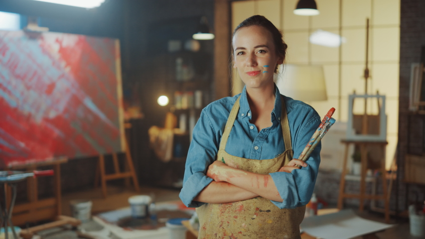 Portrait of Talented Young Female Artist Dirty with Paint, Wearing Apron and Holding Paint Brushes Looks at the Camera Smilingly. Authentic Creative Studio with Large Canvas and Equipment Lying Around | Shutterstock HD Video #1036269971