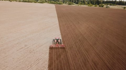 tractor plows a field aerial view