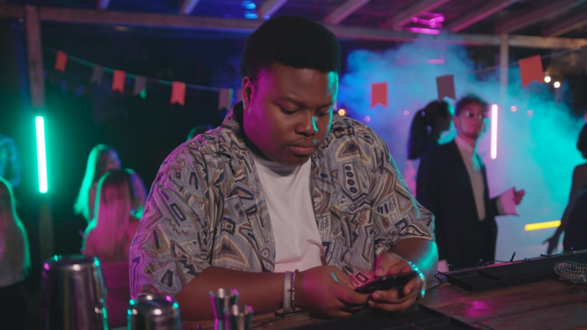 Afro-american young man in stylish look sitting on bar enjoying music with headshake using his modern smartphone on night party. | Shutterstock HD Video #1036481561