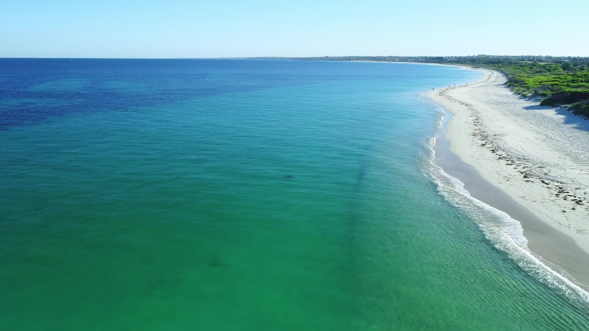 Aerial fly over views of clear blue turquoise beach with sandy white sand and clear blue skies in summer just north of Perth Western Australia at Mullaloo Whitfords beach | Shutterstock HD Video #1036537961