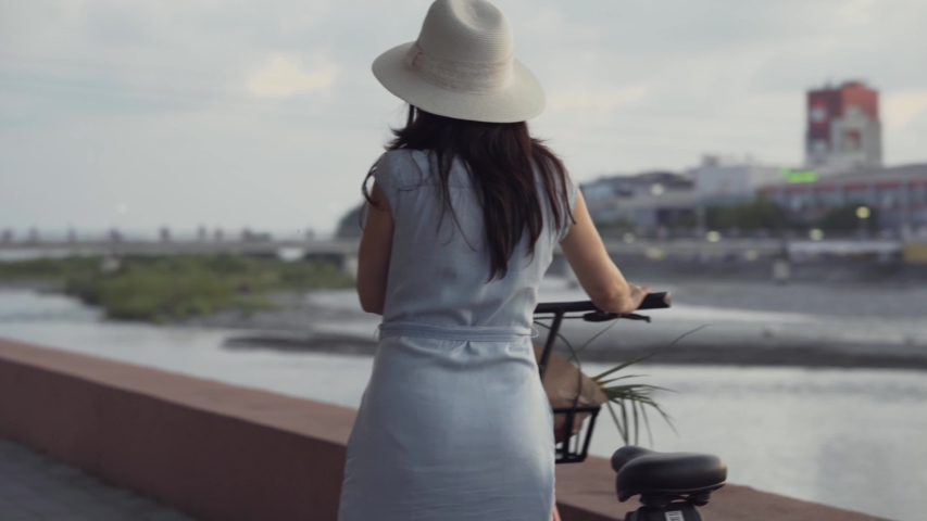 A girl in a hat and dress walking with a bike on the waterfront. Girl with a red Bicycle walking. | Shutterstock HD Video #1036640591