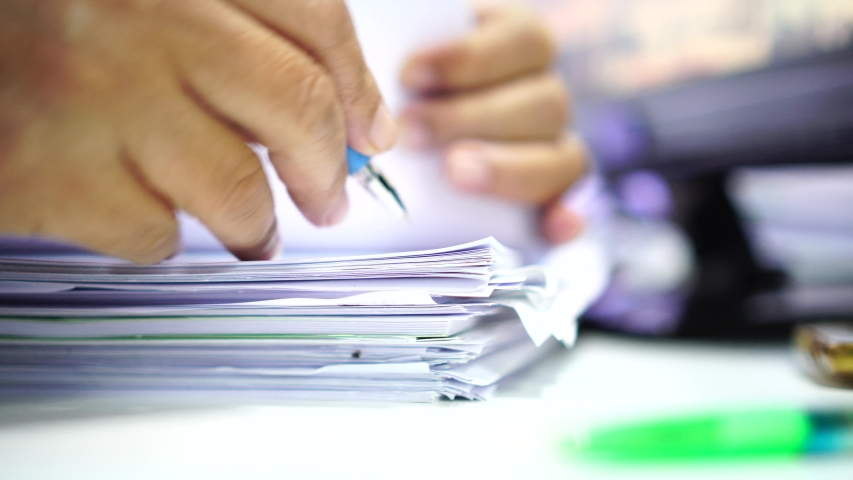 Businessman hands working in stacks of paper files for searching information on work desk office, business report papers,piles of unfinished documents achieves with clips indoor,Business concept | Shutterstock HD Video #1036734701