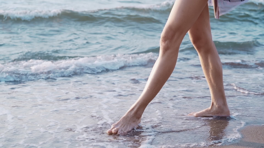 Legs of caucasian girl wearing dress and walking barefoot wet sand sea beach. Slow motion. Woman walks past by camera | Shutterstock HD Video #1036821821