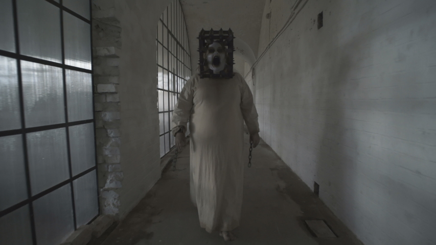 A scary ghost of a fat woman with a rusty cage on her head and with shackles on her hands wanders through gloomy corridors of an abandoned psychiatric hospital. 4K | Shutterstock HD Video #1036969721