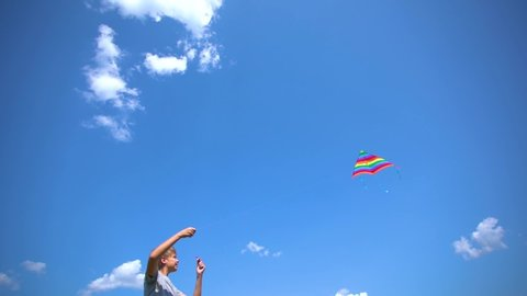 White kid playing colorful bright kite standing outdoor at sunny clear blue sky background. Slow motion full hd video footage.