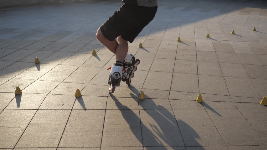 Close-up legs of a young man is professionally skating between cones on a nice evening sunset in a city park. Freestyle slalom Roller skating between cones. | Shutterstock HD Video #1037028251