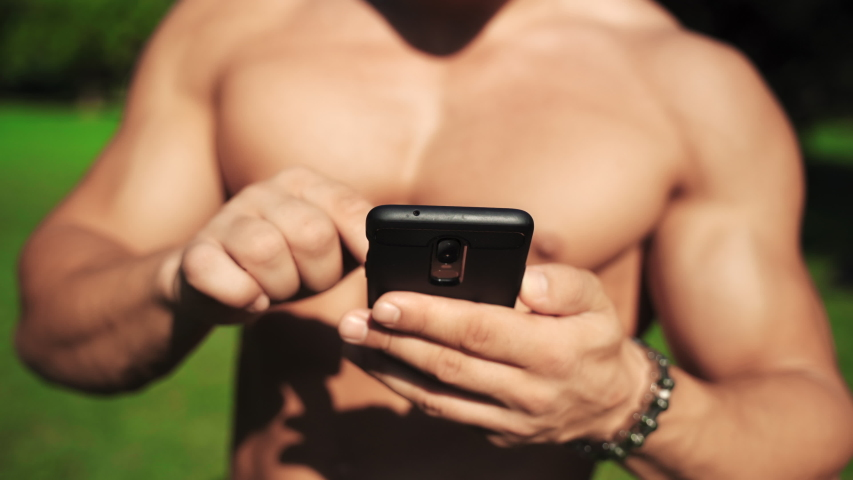 Muscular shirtless man with perfect six pack torso using his smartphone and chatting online outdoors. Young sexy coach having break after hard workout in the park. Attractive runner searching in | Shutterstock HD Video #1037037521