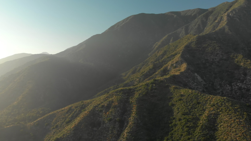 Aerial Pan and Tilt Down from a Verdant Mountain to a Winding Road | Shutterstock HD Video #1037122031