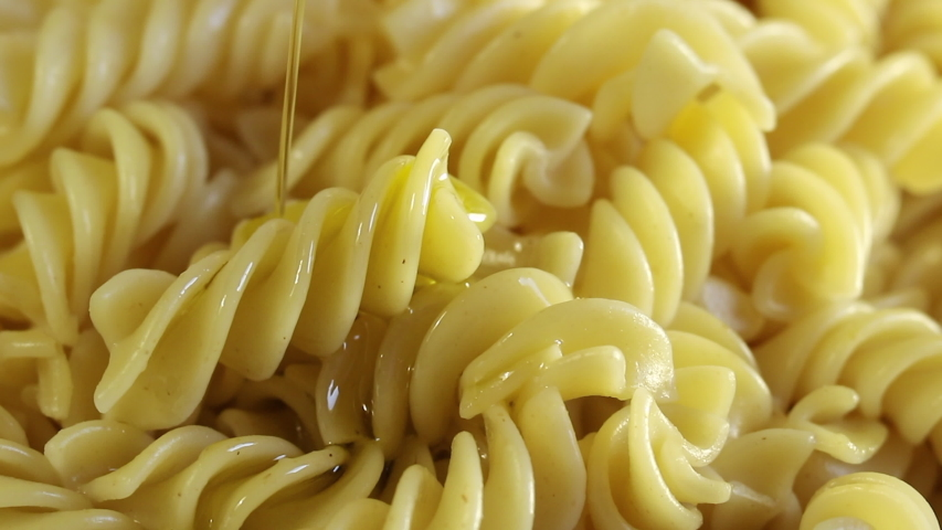 Freshly cooked yellow Italian fusilli pasta topped with olive oil. | Shutterstock HD Video #1037148491