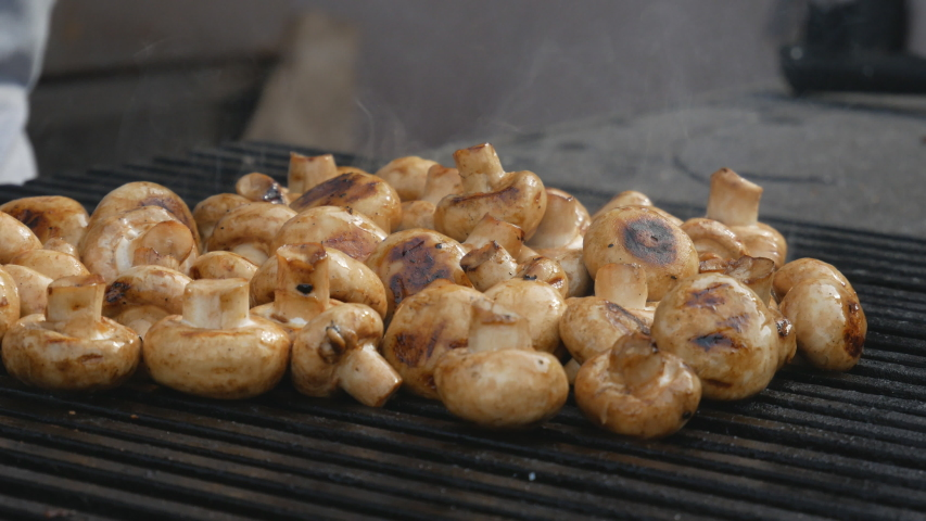 Chef's hands cooks mushrooms on the grill. Delicious, wholesome grilled food. Diet vegan barbecue. barbecue party | Shutterstock HD Video #1037174561