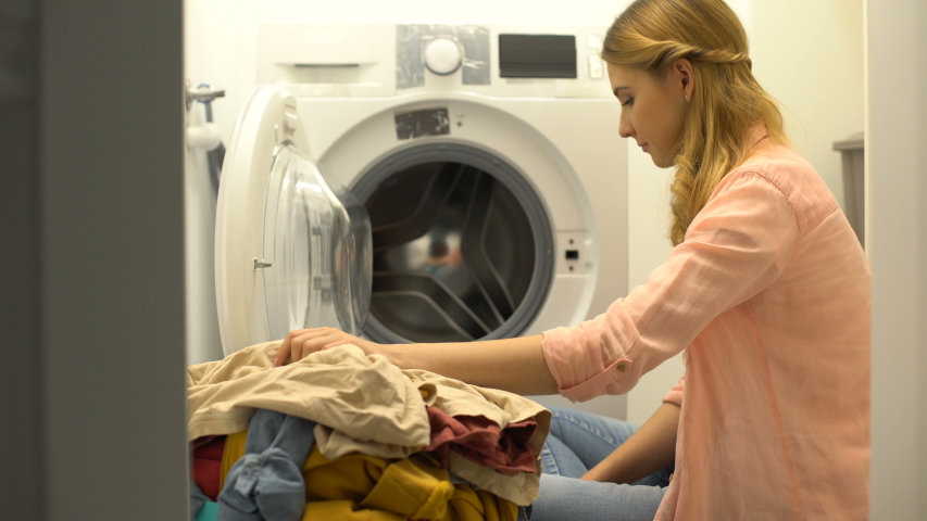 Woman putting clothes in washing machine, home laundry service, daily routine | Shutterstock HD Video #1037180801
