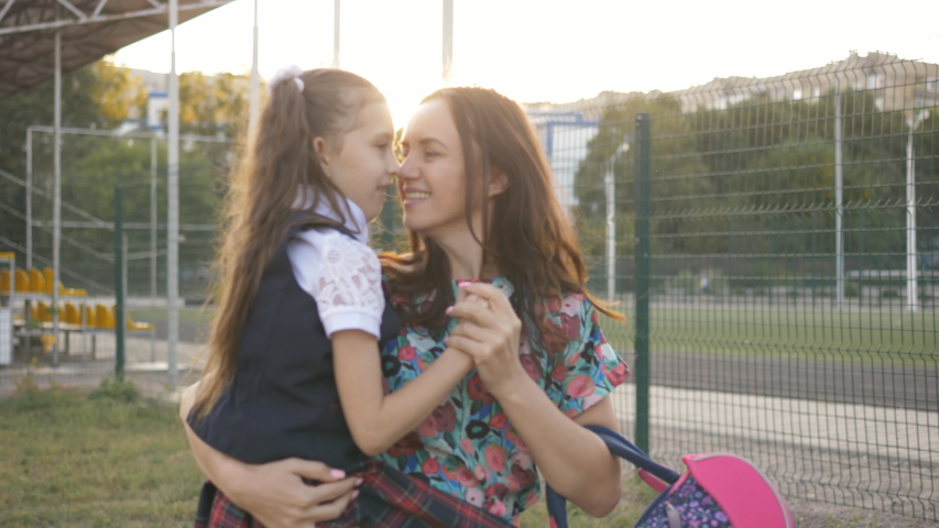 Mother and daughter come back from school after school. Mom carries a small daughter on hands. | Shutterstock HD Video #1037198801
