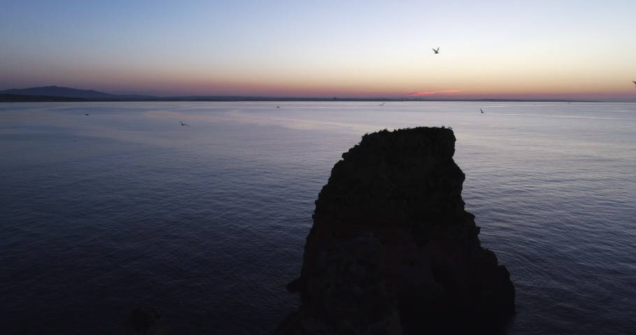 4K drone shot with parallax motion of dark limestone rock formations and sea pillars and birds flying in the sunrise at the coastline of Ponta Da Piedade in Lagos Algarve, Portugal. | Shutterstock HD Video #1037224871