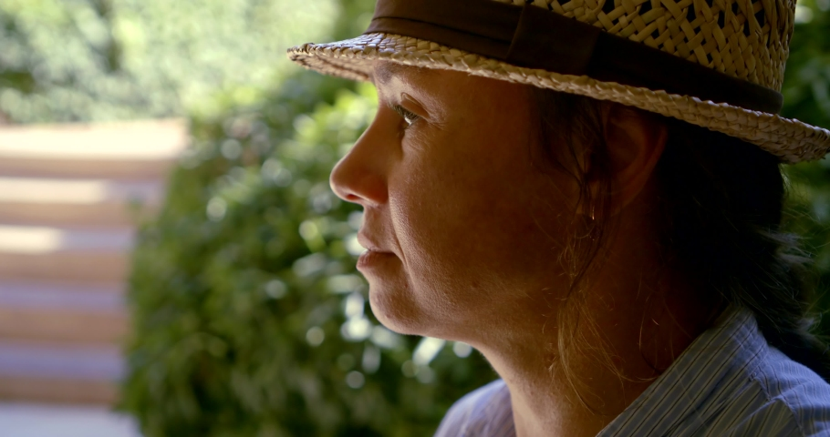Close - up portrait in profile of a dark-haired and brown-eyed middle-aged woman in a hat. She's sitting outside, drinking a drink out of a Cup. | Shutterstock HD Video #1037250641