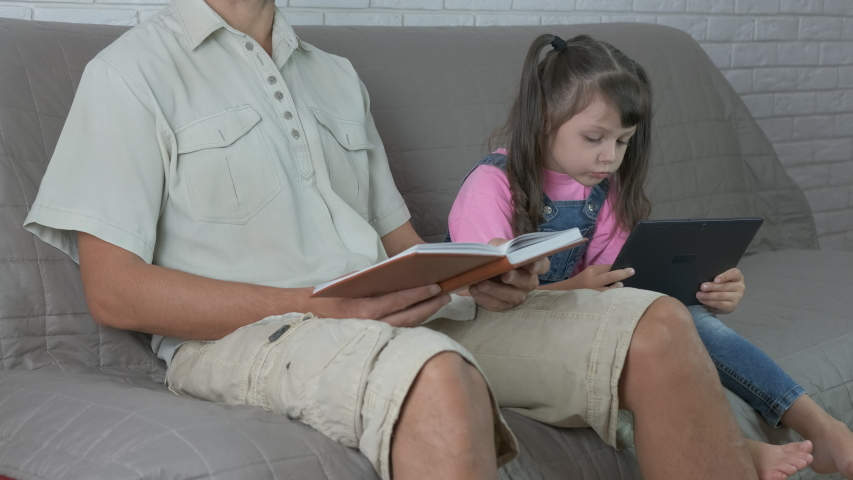 Watch the laptop. Father read a book in the bed. Little girl sit near her father with a laptop.   Shutterstock HD Video #1037324591