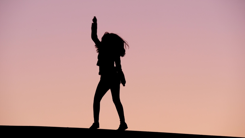 Excited young woman dance like crazy, black silhouette against pink evening sky. Happy person jump and turn around, wave hands and rise legs. Clean black figure at top of hill | Shutterstock HD Video #1037414081