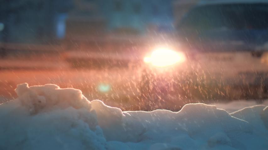 Snow falling down on night city street, illuminated by car headlights. Slow motion, 4K UHD