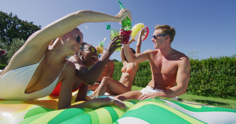 Authentic shot of young multi-ethnic friends in swimwear are relaxing on colorful inflatables and cheering with cocktails in swimming pool for celebrate a start of their vacation together. | Shutterstock HD Video #1037471441