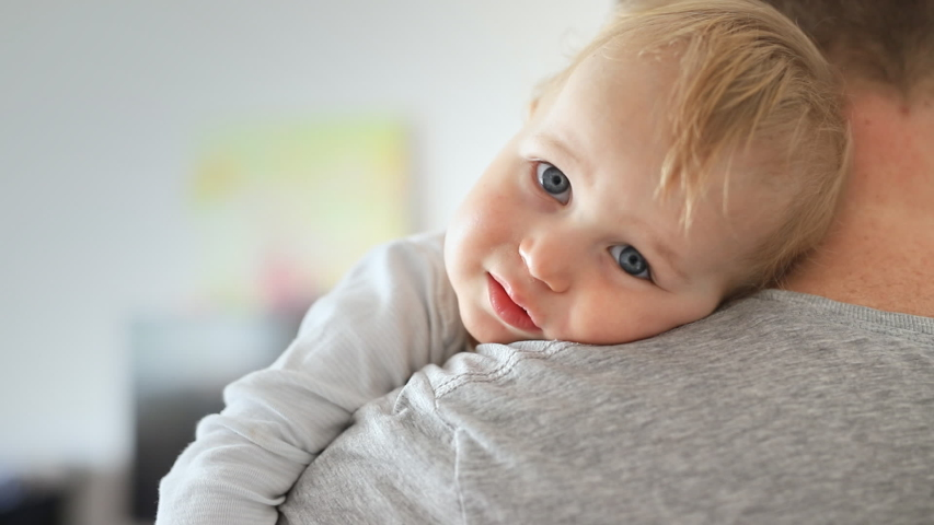 Close-up portrait of cute adorable blond caucasian toddler boy on fathers shoulder indoors. Sweet little child smiling feeling safety on daddys hand. Responsibility and childcare. happy childhood | Shutterstock HD Video #1037483231