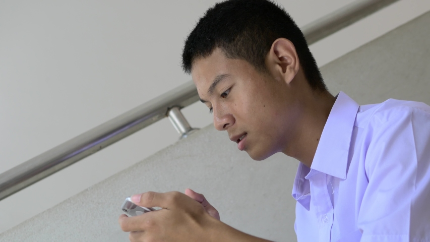 An Asian male high school student in a white uniform, who is a lot of addicted to games, is playing exciting games on his mobile phone and sitting on the school stairs. | Shutterstock HD Video #1037486501