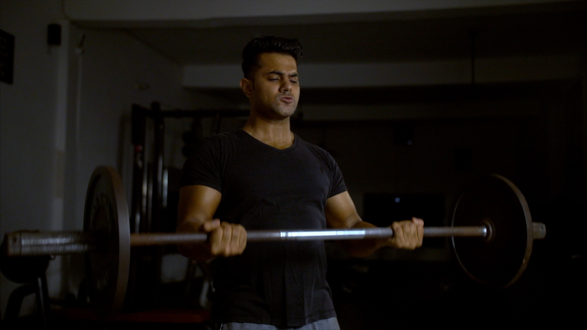 A muscular and fit Indian man doing barbell curl (bicep) exercise in the gym. | Shutterstock HD Video #1037490851