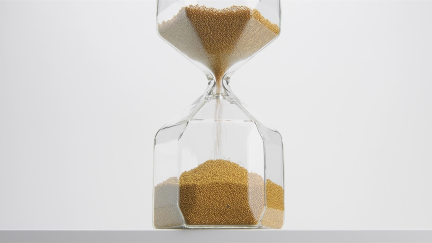 Glass sand clock on white with golden balls instead of sand falling till the end | Shutterstock HD Video #1037505731