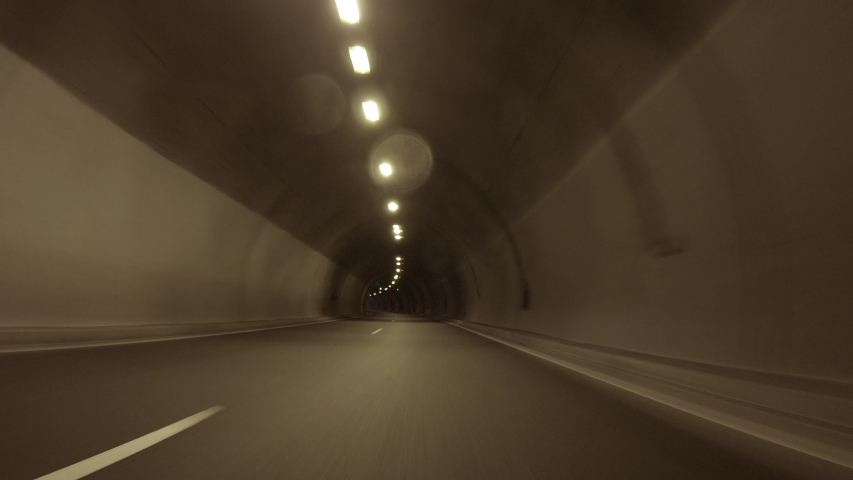 POV, Driving Plate - car driving through a tunnel with bright daylight at the end of it.