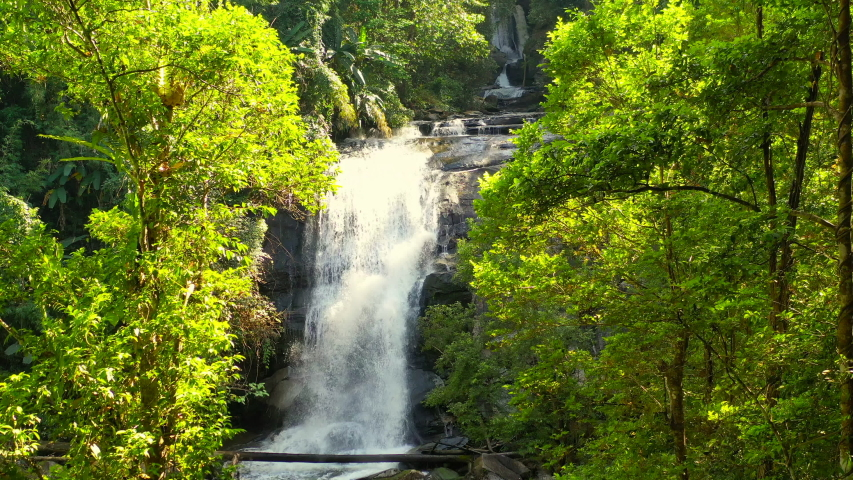Waterfall hidden in tropical rainforest jungle in national park Doi Inthanon, Asia, Thailand. 4k Aerial view