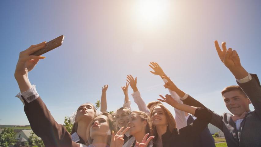 Happy high school graduates take a selfie on a sunny day. | Shutterstock HD Video #1037889731