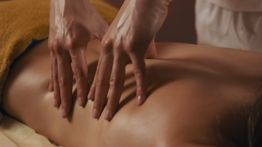 Young woman having massage in spa salon. Close-up of woman relaxing during back massage lying on massage table in slow motion. 4k, UHD | Shutterstock HD Video #1038006371