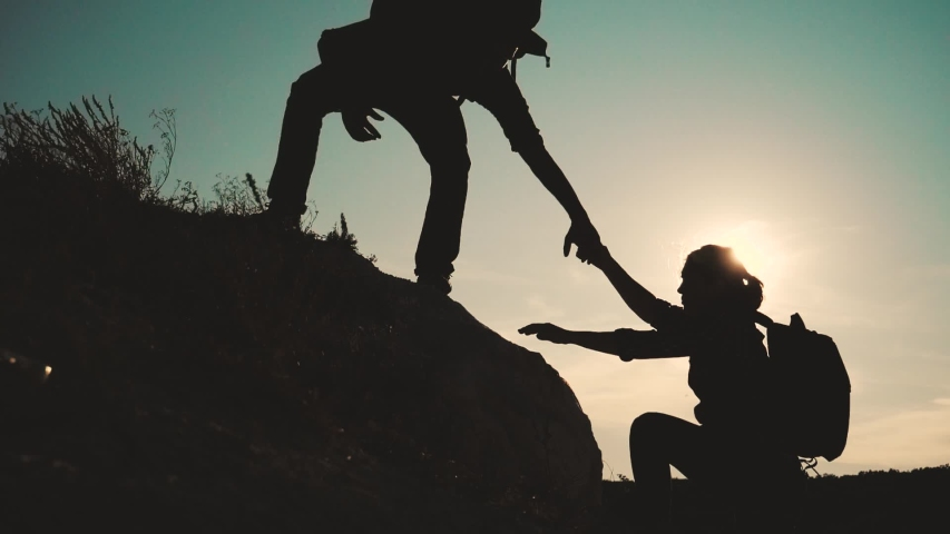 Teamwork help business travel silhouette slow motion video concept. Helping hand silhouette between two climbers. teamwork group of tourists lends a helping hand climb the cliffs mountains. couple man | Shutterstock HD Video #1038089501