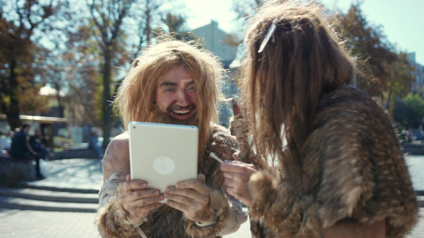 Happy aboriginal savages in animal fur using modern tablet browsing internet having fun. Hunter-gatherers of ancient tribe in modern times. Evolution.