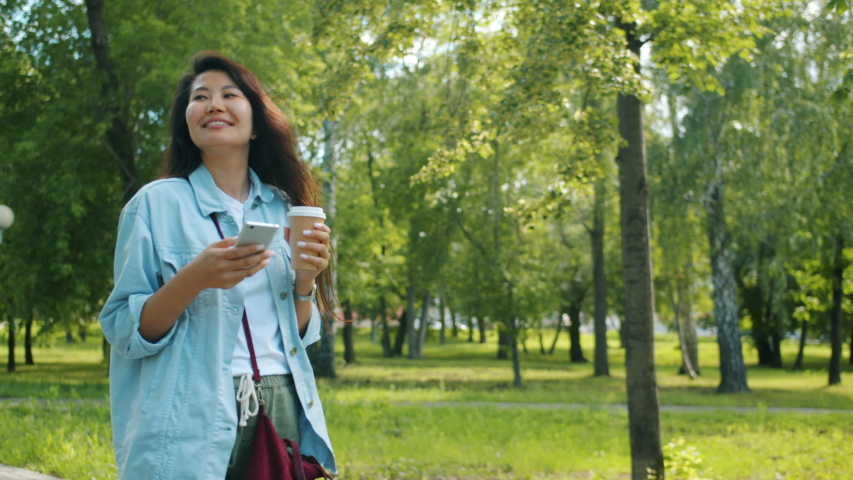 Beautiful Asian woman with long black hair is walking in park with smartphone and to go coffee smiling using device. Modern lifestyle and youth concept.   Shutterstock HD Video #1038187151