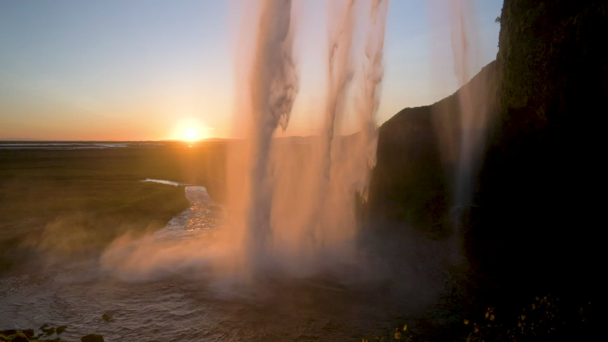 The sun slowly setting as the water falls over the cliffs at Seljalandsfoss waterfall. #1038222221