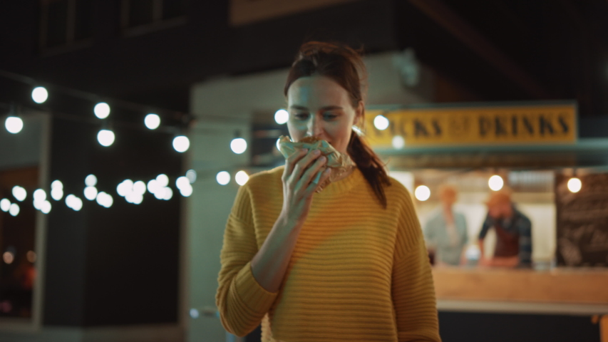 Beautiful Young Female Walks Away from a Food Truck with a Delicious Fresh Beef Burger. She's Happy with Hew Food and Takes a Biet. Commercial Kiosk is Selling Street Food on a Modern Cool Street. | Shutterstock HD Video #1038373991