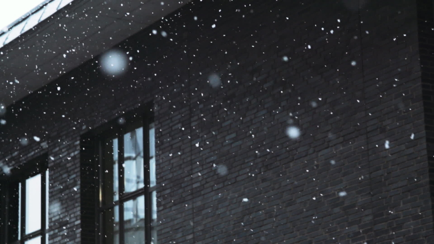 Large snowflakes slowly falling near old office building exterior. | Shutterstock HD Video #1038422471