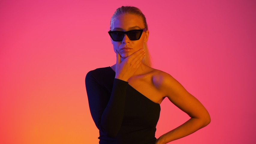Thoughtful pretty woman rubs her chin thinking about new idea. Neon light and vivid colors. Young attractive blond girl with thoughtful face isolated on red background. Beauty and confiden?? concept | Shutterstock HD Video #1038436991