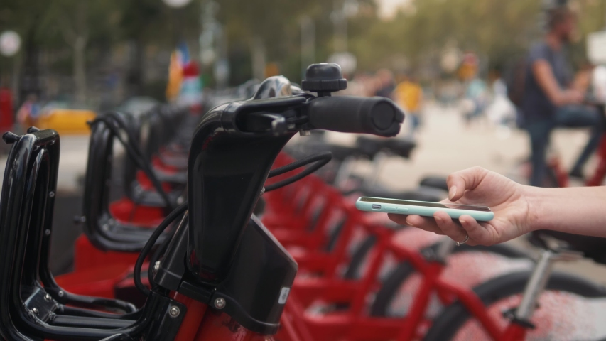 Woman take Electric Kick scooter or bike bicycle in sharing parking lot, tourist phone application. New sharing business project started in city, eco transportation | Shutterstock HD Video #1038525551