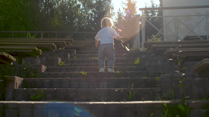 Small blond boy climbing up stairs in an outdoor theater. Lens flare, rear view. Slow motion, steadicam shot. | Shutterstock HD Video #1038601181