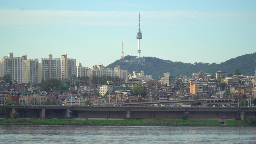 Iconic city view of Seoul, South Korea in the golden hour on a sunny day. This medium angle shot features the Namsan tower, Han river, Banpo bridge, key city buildings and the mountains | Shutterstock HD Video #1038631241