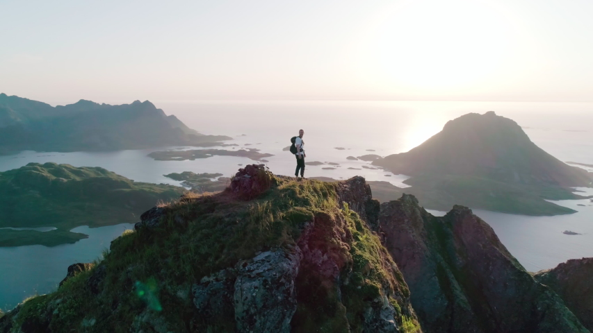 4K drone shot with orbit motion of Norwegian climber celebrating climbing top of a mountain by raising his arms to the sky with panorama sunset background view of Lofoten and Vesterålen, Norway. | Shutterstock HD Video #1038701141