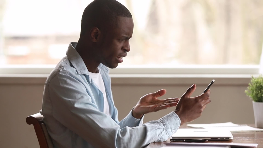Indignant african man sit at desk makes videocall holds smartphone points on screen talking gesticulating, black guy having problems with broken device feels outraged, low internet no network concept | Shutterstock HD Video #1038796271