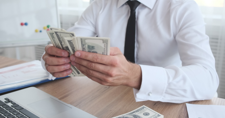 Businessman counting his salary sitting at office | Shutterstock HD Video #1038813401